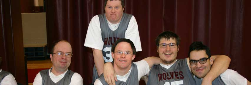 Members of the NWCSRA Wolves Special Olympics Basketball team taking a water break on the bench